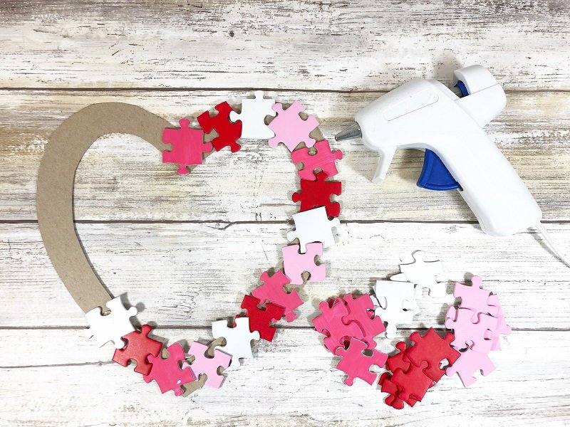 Glue a layer of puzzle pieces on the base Puzzle Piece Heart Shaped Wreath Creatively Beth #creativelybeth #dollartreecrafts #heart #valentinesdaycrafts #kidscrafts