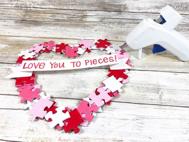 Atach banner to wreath Puzzle Piece Heart Shaped Wreath Creatively Beth #creativelybeth #dollartreecrafts #heart #valentinesdaycrafts #kidscrafts