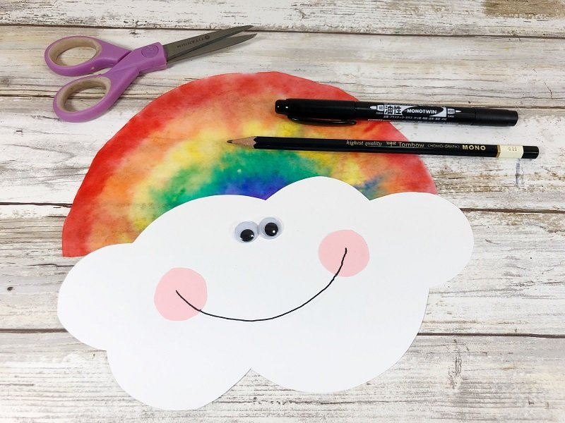 Add face to cloud and attach rainbow Creatively Beth #cretivelybeth #dollartreecrafts #kidscrafts #colorblending #rainbowcrafts