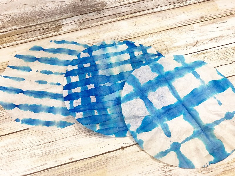 Unfold to reveal the Shibori Tie Dye patterns Creatively Beth #creativelybeth #teidye #techniques #tombow #tombowdualbrushpens #dollartreecrafts #kidscrafts