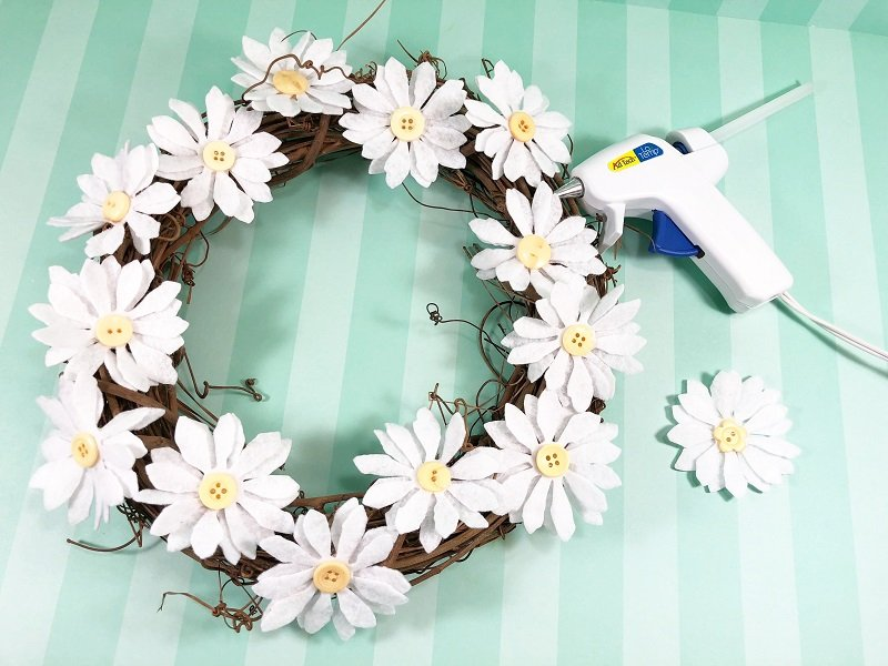 Attach completed daisies to wreath with glue gun Creatively Beth #creativelybeth #daisy #wreath #mothersdaycraft #kidscraft #feltcraft #feltflowers