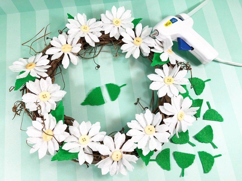 Trim felt leaves and tuck in under the daisy flowers Creatively Beth #creativelybeth #daisy #wreath #mothersdaycraft #kidscraft #feltcraft #feltflowers