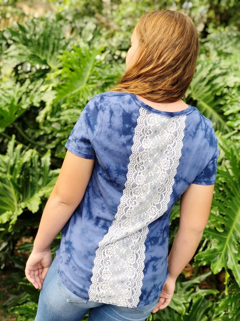 Girl wearing a blue colored tee shirt with white lace trim attached to the back with fabric glue. #creativelybeth #upcycled #clothing #lace #tshirt #teeshirt