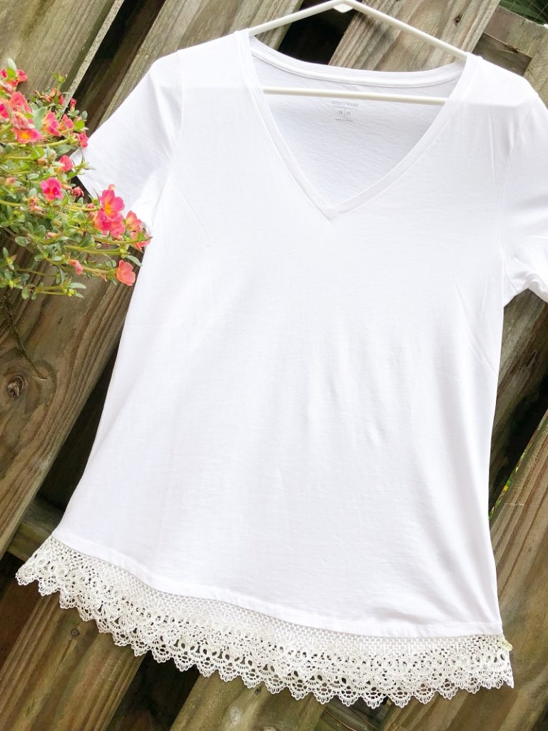 Girl wearing a white colored tee shirt with white lace trim attached to the bottom hem with fabric glue. #creativelybeth #upcycled #clothing #lace #tshirt #teeshirt