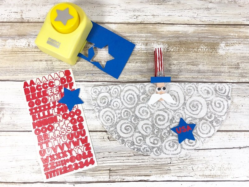 Punch a blue star from craft paper and add red USA letter stickers Creatively Beth #creativelybeth #kidscrafts #unclesam #patrioticcrafts