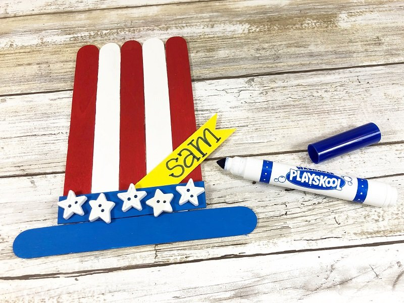 Add a name on a bright yellow tag and washable marker Creatively Beth #creativelybeth #craftsticks #kidscrafts #patrioticcrafts #redwhiteandblue