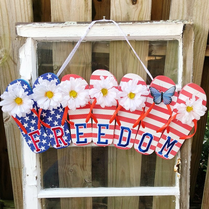 Stars and Stripes Flip Flop Sign hanging on an old window in front of a wooden fence Creatively Beth #creativelybeth #flipflopsign #freedom #recycle #upcycle #dollartree #craft
