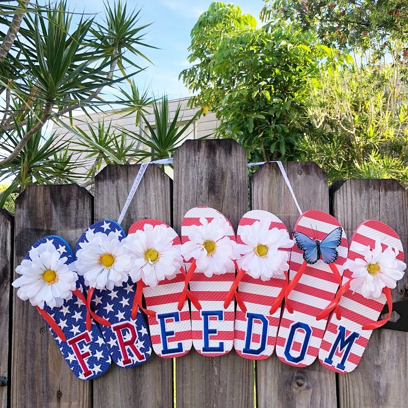 Red, White and Blue Flip Flop Freedom Sign hanging on a wooden fence with green trees and a blue sky Creatively Beth #creativelybeth #flipflopsign #freedom #recycle #upcycle #dollartree #craft
