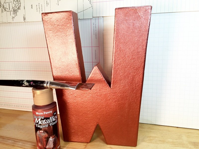 Paint a paper mache monogram letter W with copper metallic paint with a paintbrush Creatively Beth #recycled #crafts #monogram #pennies