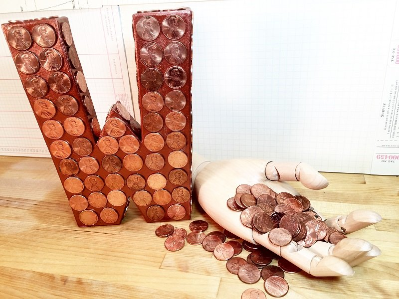 Pennies glued to a monogram letter W and a mechanical hand holding pennies Creatively Beth #recycled #crafts #monogram #pennies