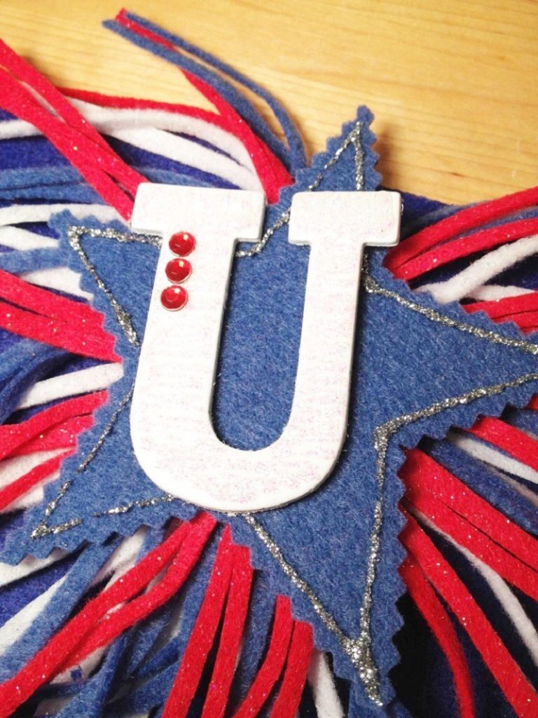 Cut stars from blue felt then layer on USA letters, glitter glue and rhinestones to finish the DIY Banner Creatively Beth #creativelybeth #fourthofjuly #patriotic #crafts #feltcrafts #quickandeasy