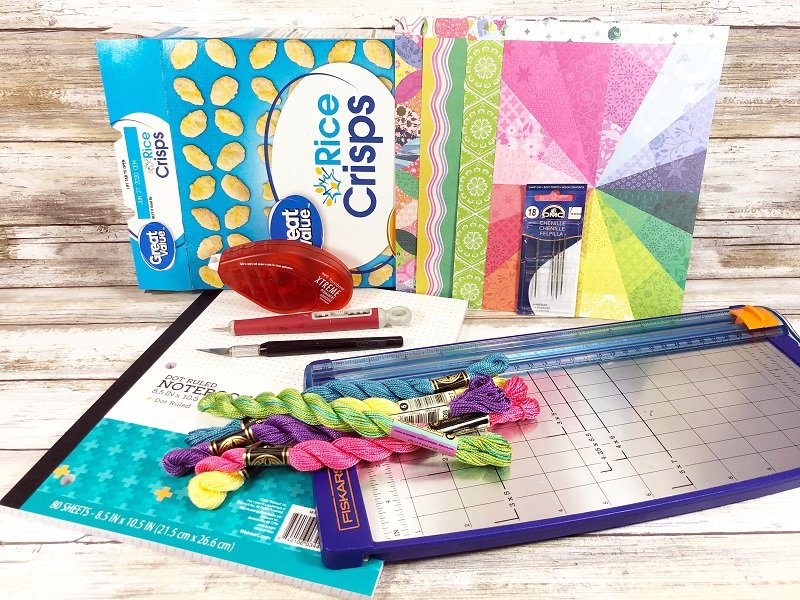 Materials needed to create Four notebooks made from a recycled cereal box with colorful patterned paper and buttons #creativelybeth #recycled #crafts #notebooks #journals #upcycled