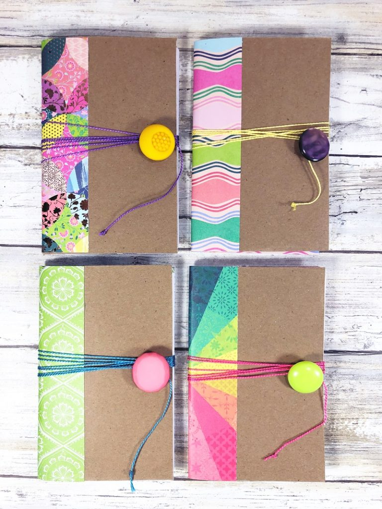 Four notebooks made from a recycled cereal box with colorful patterned paper and buttons #creativelybeth #recycled #crafts #notebooks #journals #upcycled