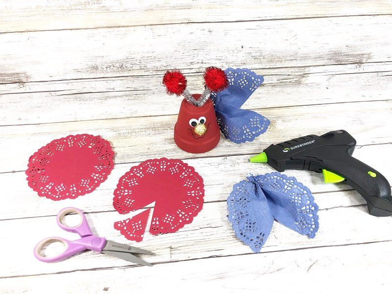 Create love bug wings from colored doilies Creatively Beth #creativelybeth #dollartreecrafts #patrioticcrafts #claypotcrafts #fourthofjuly