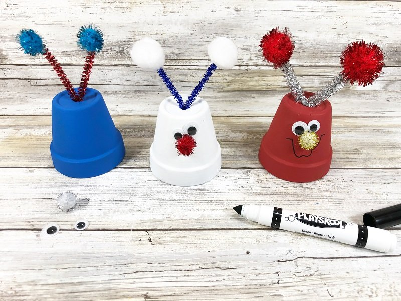Add wiggle eyes, pom pom nose and draw on mouth with black marker Creatively Beth #creativelybeth #dollartreecrafts #patrioticcrafts #claypotcrafts #fourthofjuly