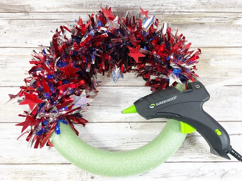 Wrap a second red white and blue garland around wreath form and secure with glue Creatively Beth #creativelybeth #patriotic #crafts #dollartree #fourthofjuly #quickandeasy