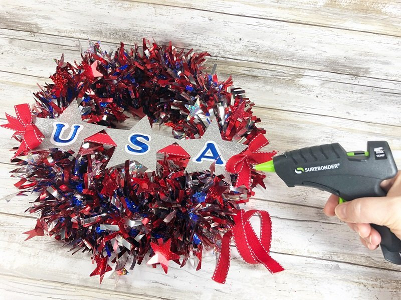 Attach banner to wreath with hot glue gun and accent with red ribbon bows Creatively Beth #creativelybeth #patriotic #crafts #dollartree #fourthofjuly #quickandeasy