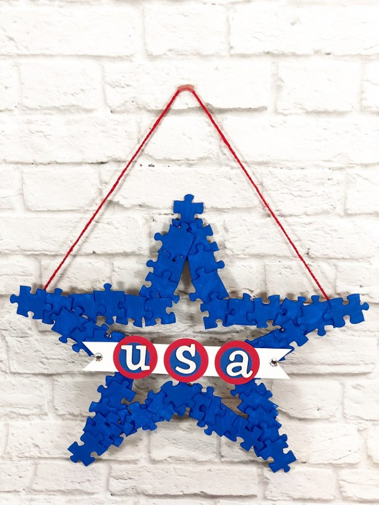Red white and blue painted puzzle pieces to create a star wreath Creatively Beth #creativelybeth #recyclecrafts #upcycledcrafts #fourthofjulycrafts #kidscrafts
