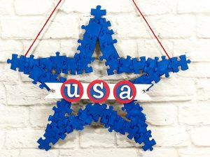 puzzle piece star wreath painted red white and blue Creatively Beth #creativelybeth #recyclecrafts #upcycledcrafts #fourthofjulycrafts #kidscrafts