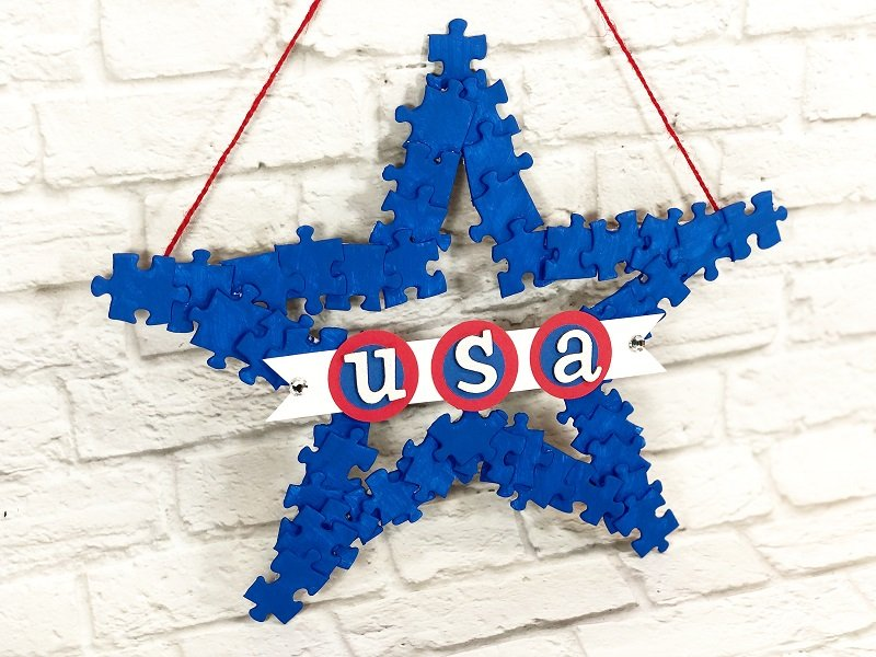 Recycled puzzle pieces are painted blue and become a star wreath for the fourth of july Creatively Beth #creativelybeth #recyclecrafts #upcycledcrafts #fourthofjulycrafts #kidscrafts