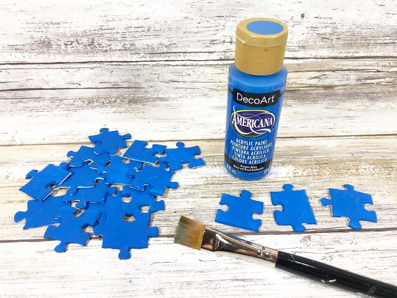Paint all the dollar tree puzzle pices with blue craft paint Creatively Beth #creativelybeth #recyclecrafts #upcycledcrafts #fourthofjulycrafts #kidscrafts