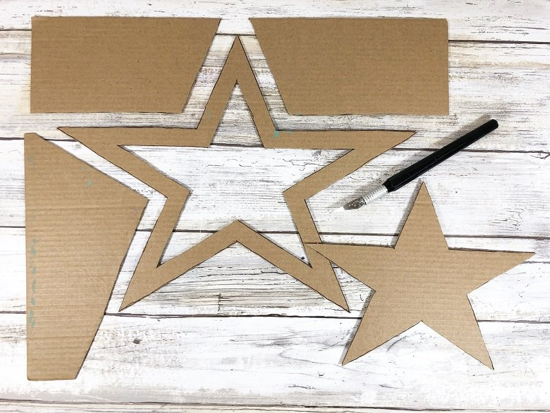 Cut out a large star shape with scissors and a craft knife to create a base for the wreath Creatively Beth #creativelybeth #recyclecrafts #upcycledcrafts #fourthofjulycrafts #kidscrafts