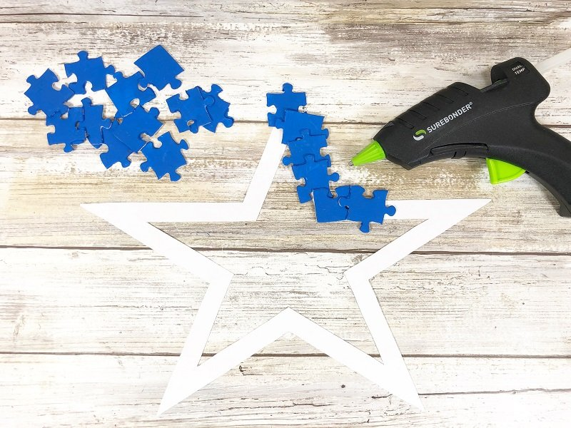 Apply a layer of blue painted puzzle pieces to the star shape Creatively Beth #creativelybeth #recyclecrafts #upcycledcrafts #fourthofjulycrafts #kidscrafts