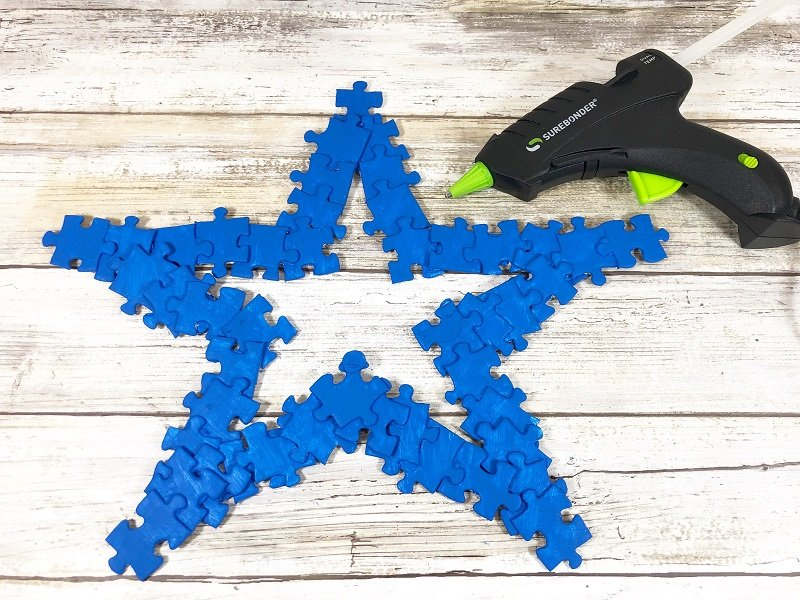 Glue a second layer of puzzle pieces on top of the first with hot glue Creatively Beth #creativelybeth #recyclecrafts #upcycledcrafts #fourthofjulycrafts #kidscrafts