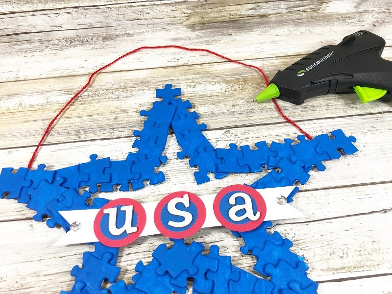 Attach the USA banner to the center of the star wreath Creatively Beth #creativelybeth #recyclecrafts #upcycledcrafts #fourthofjulycrafts #kidscrafts