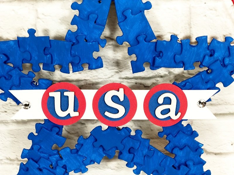 Detail of white USA letters detail on red and blue circles to create a banner Creatively Beth #creativelybeth #recyclecrafts #upcycledcrafts #fourthofjulycrafts #kidscrafts