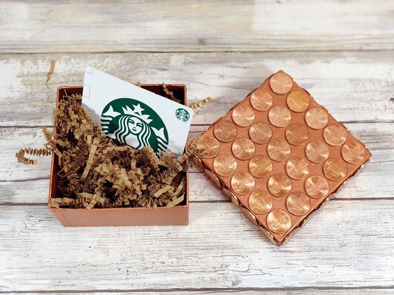 Recycled pennies glued to the lid of a square gift box with paper shred and a Starbucks gift card Creatively Beth #creativelybeth #recycled #upcycled #penny #crafts #giftbox