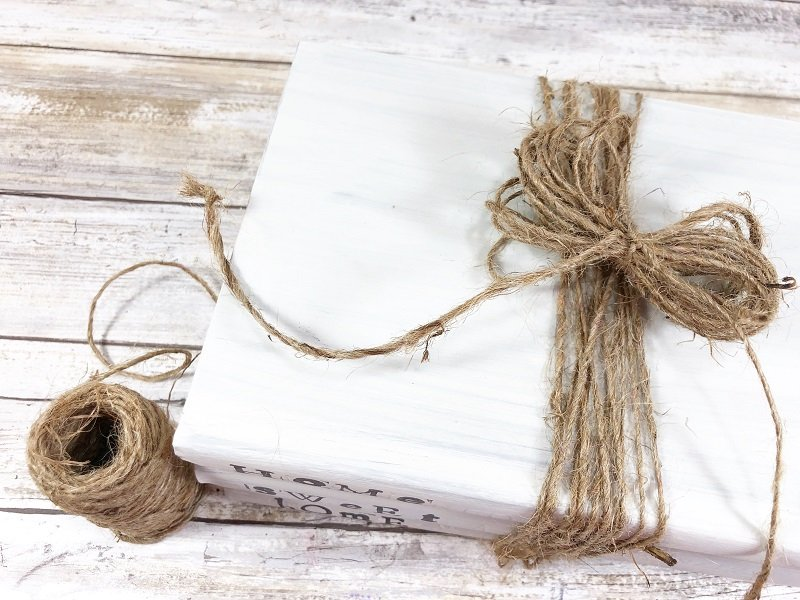 Place twine loops in the middle of the book stack and secure with a knot Creatively Beth #creativelybeth #dollartreecraft #homedecor #bookstack #diy