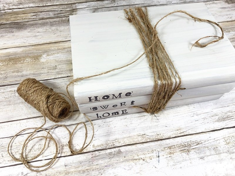 Wrap dollar tree twine around all three books about a dozen times secure with a knot Creatively Beth #creativelybeth #dollartreecraft #homedecor #bookstack #diy