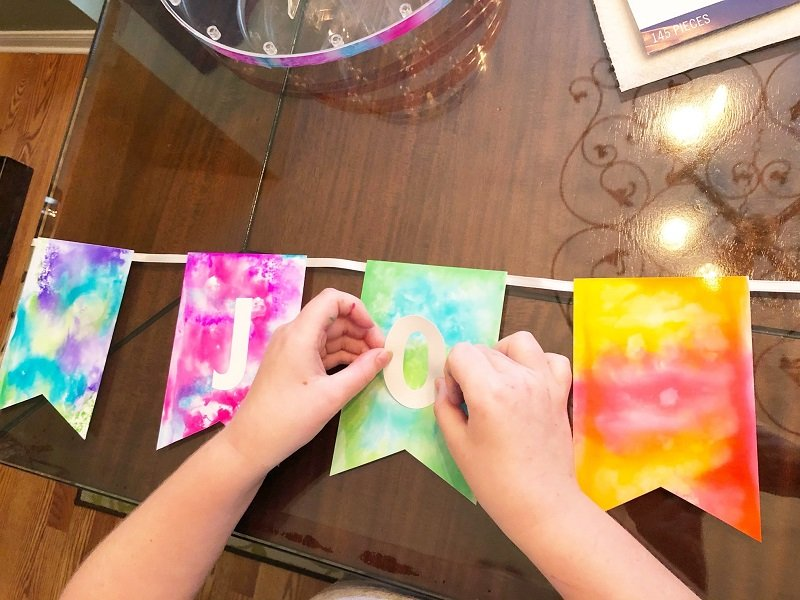 Attach tie dye paper to ribbon to create a banner with letter stickers Creatively Beth #creativelybeth #tiedye #birthdayparty #cupcakes #deflecto #cupcakestand #tombowdualbrushpens