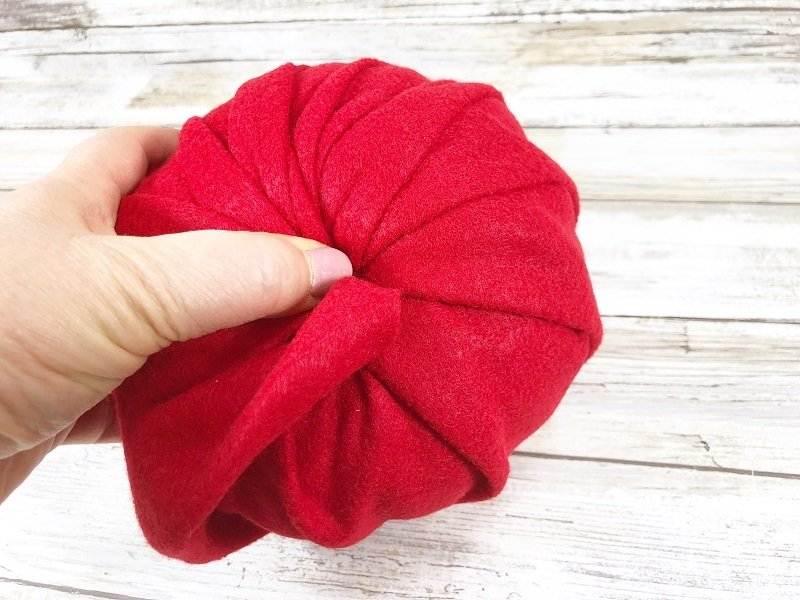 Pull gently and fold all felt into the hold tightly Creatively Beth #creativelybeth #dollartreecrafts #halloweencrafts #pumpkincrafts #rainbowcrafts #createwithkunin