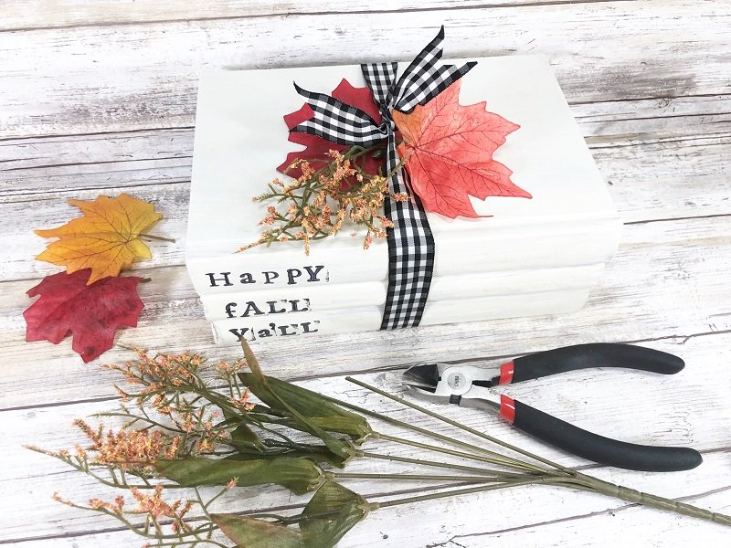 Cut leaves and flowers from a Dollar Tree stem and tuck into the ribbon Creatively Beth #creativelybeth #dollartree #creaft #bookstack #fall #autumn #homedecor