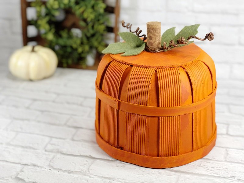 How to make a DIY Pumpkin Bushel Basket Fall Decor with orange paint, a wine cork ste, wite vines and felt leaves on a white background Creatively Beth #creativelybeth #dollartree #craft #falldecor #bushelbasket #pumpkin #craft