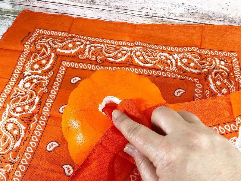 Layout bandana on a flat surface and insert one corner of the fabric into the hole Creatively Beth #creativelybeth #dollartree #bandanacrafts #crafts #pumpkin #falldecor #autumndecor