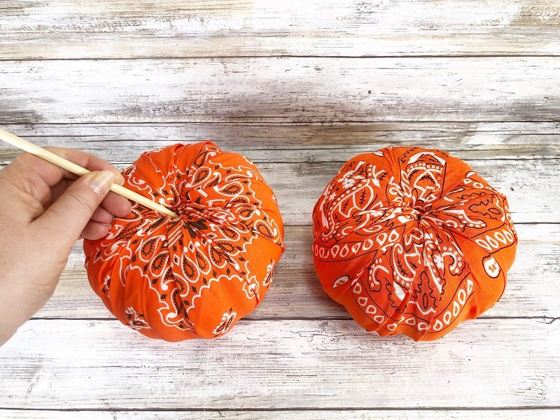 Use a chopstick or pencil to poke the fabric into the hole Creatively Beth #creativelybeth #dollartree #bandanacrafts #crafts #pumpkin #falldecor #autumndecor