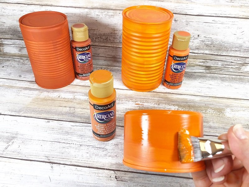 Topcoat each tin can with different colors of orange acrylis paint with a flat paintbrush Creatively Beth #CreativelyBeth #recycledcrafts #fallcrafts #pumpkincrafts #autumncrafts