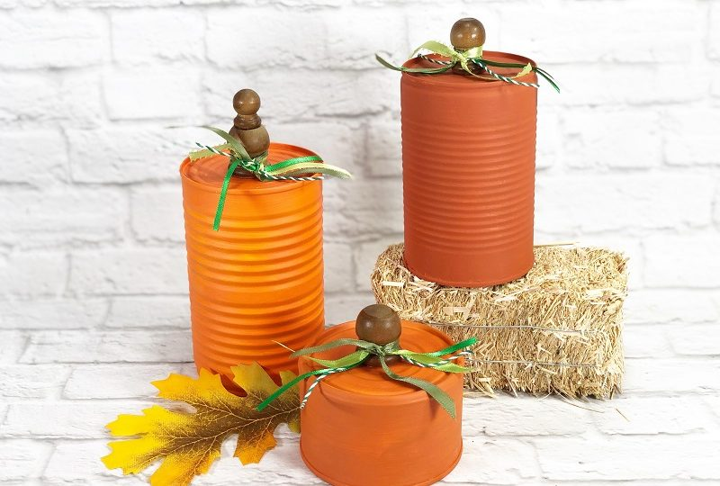 How to Recycle Tin Can Pumpkins for Autumn Creatively Beth Three orange cans sitting on a hay bale on a brick background #CreativelyBeth #recycledcrafts #fallcrafts #pumpkincrafts #autumncrafts