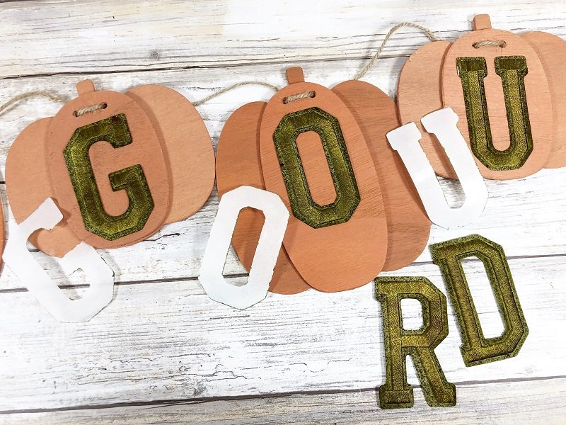 Peel backer from adhesive letters and attach to remaining pumpkins Creatively Beth #creativelybeth #fall #garland #pumpkin #crafts #ohmygourd