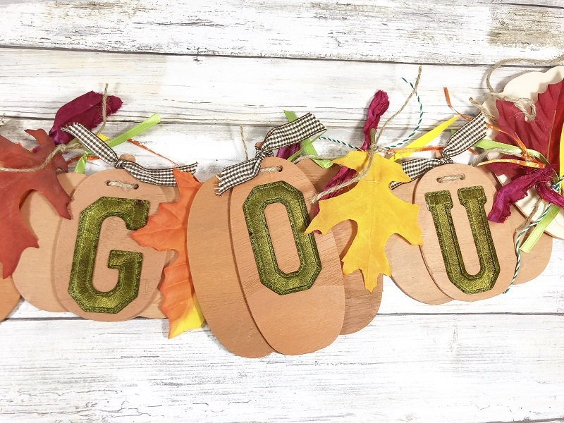 Tie silk leaves and ribbon in between wooden pumpkins Creatively Beth #creativelybeth #fall #garland #pumpkin #crafts #ohmygourd