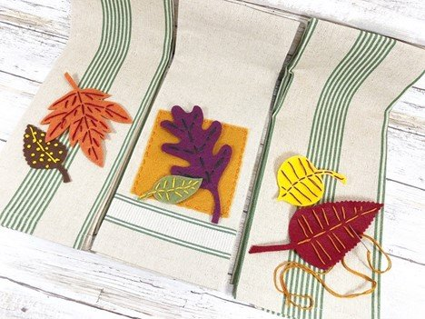 Position two leaves onto each towel Creatively Beth #creativelybeth #embroidery #handsewn #autumndecor #feltcrafts #fallleaves #easycrafts