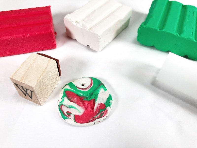 Take remaining clay scraps and roll together to marble. Flatten into a circle and press alphabet stamp into clay to create a monogram Creatively Beth #creativelybeth #polymerclay #christmas #ornaments