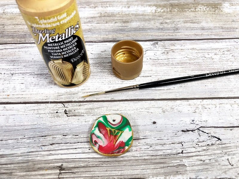 Apply gold paint to the monogram and edges Creatively Beth #creativelybeth #polymerclay #christmas #ornaments
