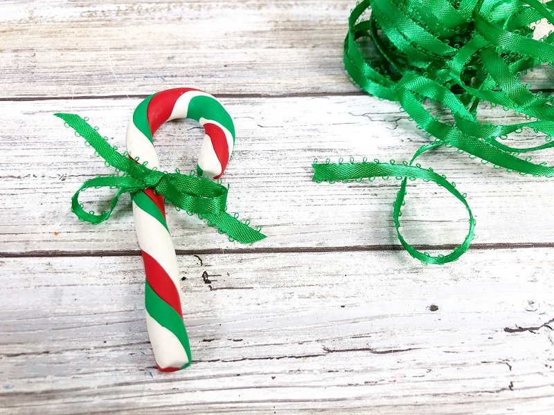 Tie a green satin bow around the candy cane ornament to finish Creatively Beth #creativelybeth #polymerclay #christmas #ornaments