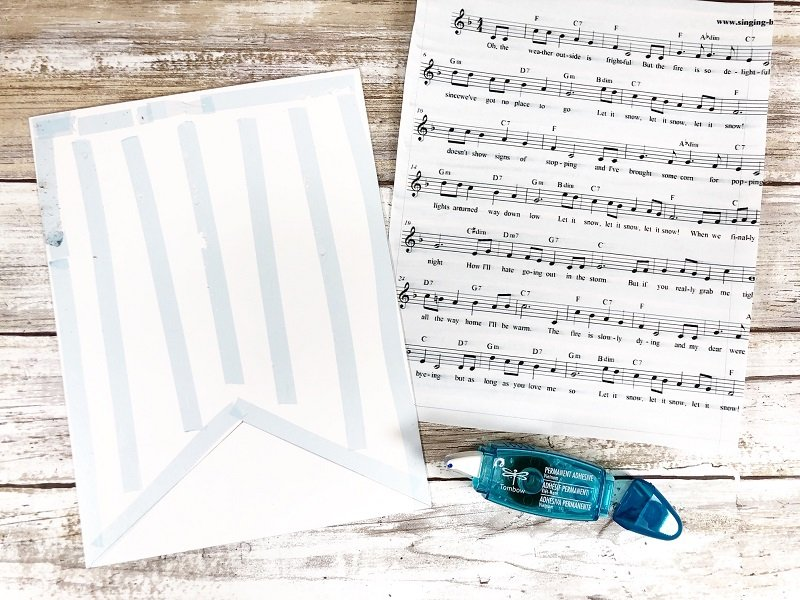 Attach music sheet to mixed media paper with Tombow Mini Power Tape Creatively Beth #creativelybeth #tombow #handlettered #glitter #banner #adhesives