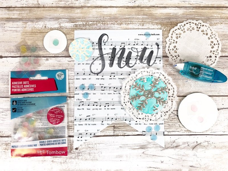Add depth by stacking Tombow Adhesive Dots on back of snowflakes Creatively Beth #creativelybeth #tombow #handlettered #glitter #banner #adhesives