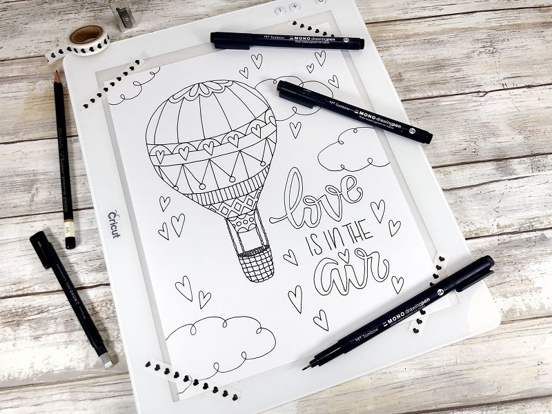 Using the Cricut BrightPad for inking in the Love is in the Air Coloring Page by Creatively Beth #creativelybeth #valentinesday #freeprintable #coloringpage #handdrawn #handlettered